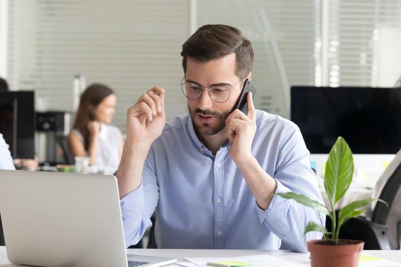 biuro - człowiek z telefonem przy komputerze